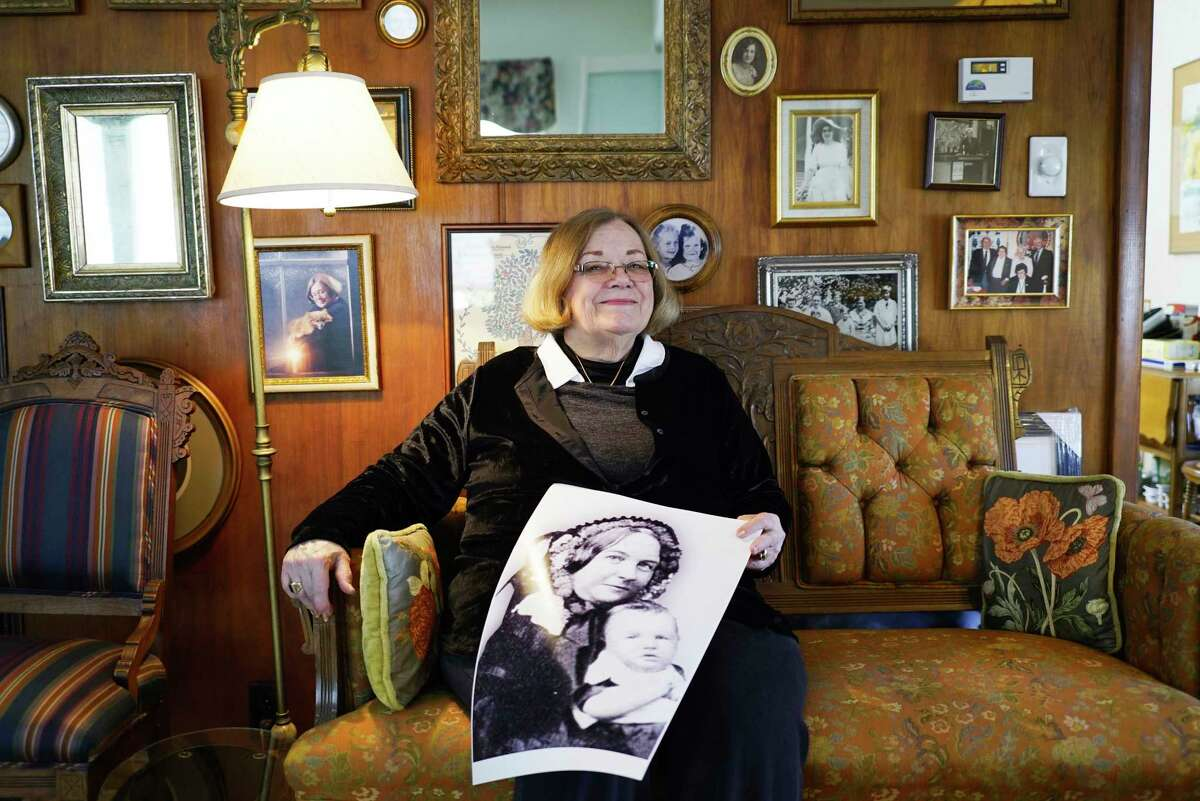 Sandy Maceyka poses at her home with a photo of Elizabeth Cady Stanton with one of her children on Thursday, March 5, 2020, in Johnstown, N.Y. Maceyka is sitting on a couch from the Cady Stanton time period. (Paul Buckowski/Times Union)