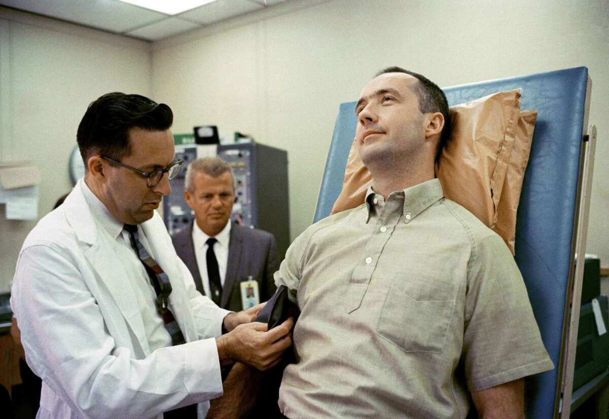 Dr. Charles A. Berry prepares to check the blood pressure of astronaut James A. McDivitt, command pilot for the Gemini-Titan 4 spaceflight, on June 1, 1965.
