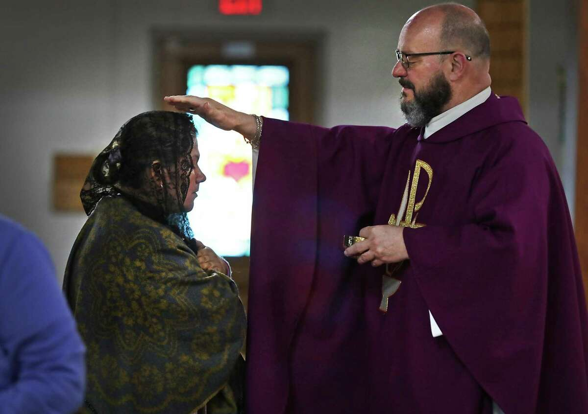 Archbishop Gustavo García-Siller announced Thursday that the Catholic churches in the Archdiocese of San Antonio will continue to practice social distancing and limit gatherings to 10 people or fewer until May 18. In the photo, during a recent Mass at Our Lady of Perpetual Help Catholic Church, Father Kevin Fausz blesses Juanita Mancilla.