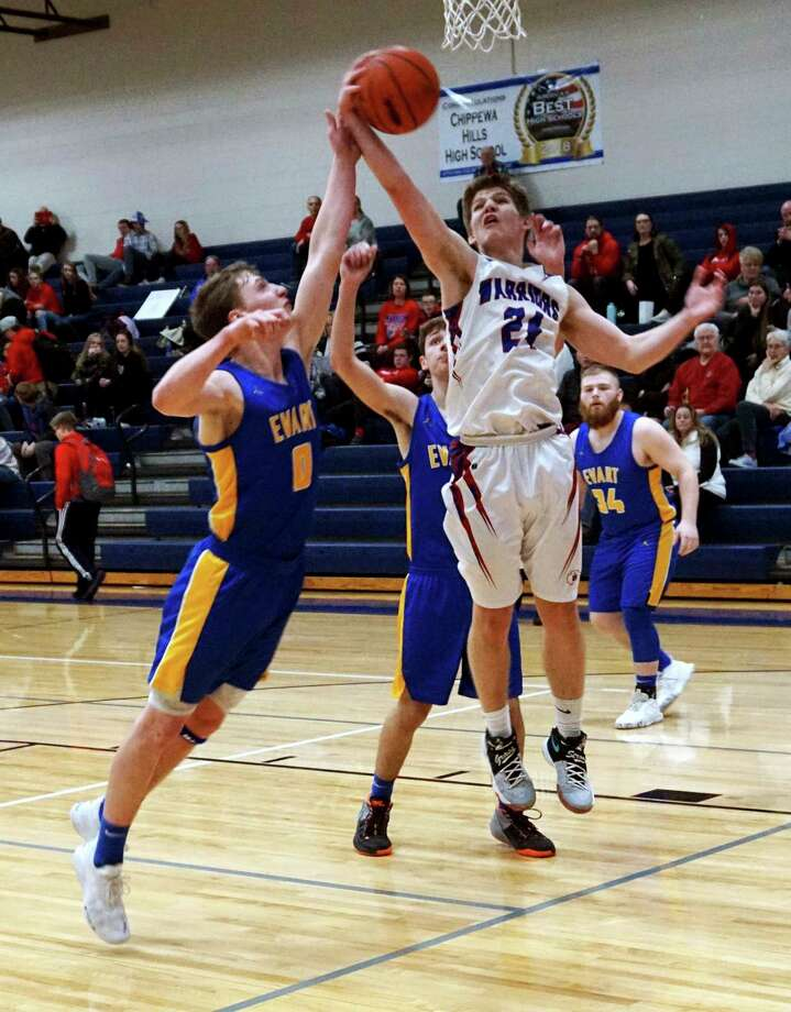 Junior Levi Rogers of Chippewa Hills attempts a layup while Evart senior Donavin Regan goes up for the block during Evart's 70-39 win over the Warriors on Thursday night. (Pioneer photo/Joe Judd)