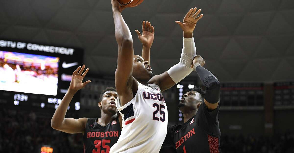 Connecticut's Josh Carlton (25) goes up for a basket against Houston's Fabian White Jr. (35) and Chris Harris Jr. (1) in the first half of an NCAA college basketball game, Thursday, March 5, 2020, in Storrs, Conn. (AP Photo/Jessica Hill)