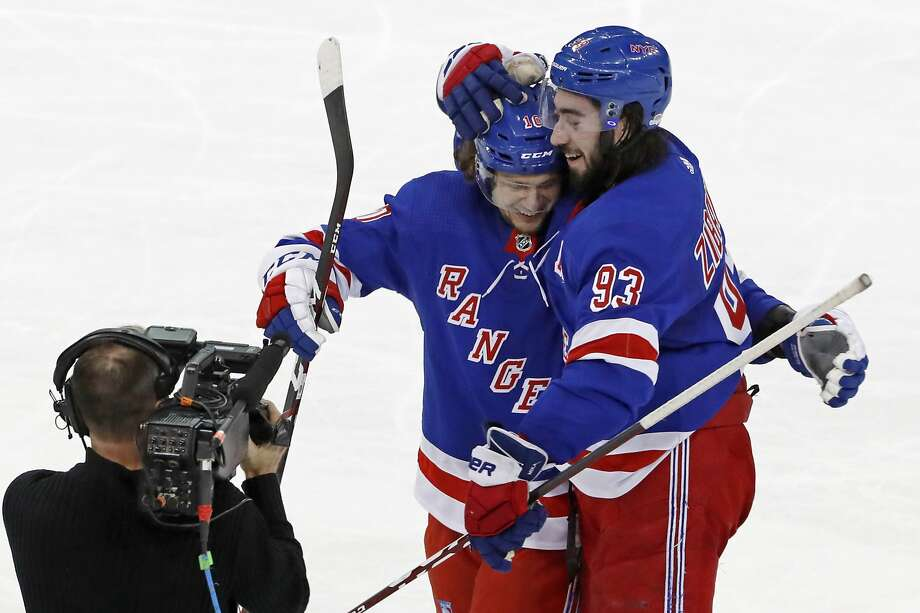 Rangers center Mika Zibanejad (93) celebrates with Artemi Panarin after scoring in overtime, his fifth goal of the game. Photo: Kathy Willens / Associated Press