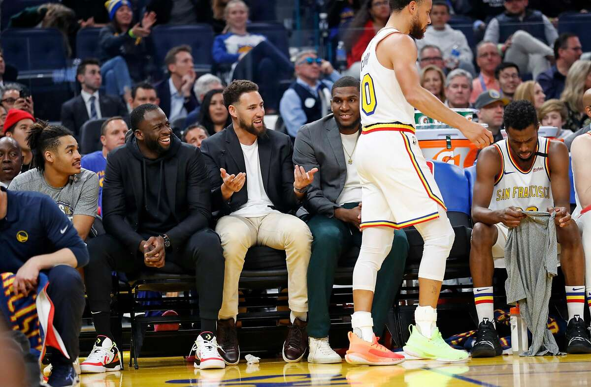 Golden State Warriors' Draymond Green, Klay Thompson and Kevon Looney react to Stephen Curry in 2nd quarter against Toronto Raptors during NBA game at Chase Center in San Francisco, Calif., on Thursday, March 5, 2020.