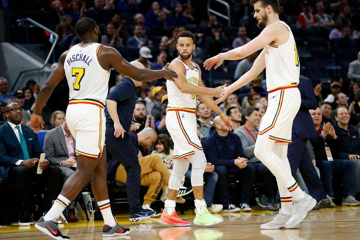 Golden State Warriors' Stephen Curry is congratulated by Eric Paschall and Dragan Bender after a Curry 3-pointer in 2nd quarter against Toronto Raptors during NBA game at Chase Center in San Francisco, Calif., on Thursday, March 5, 2020.