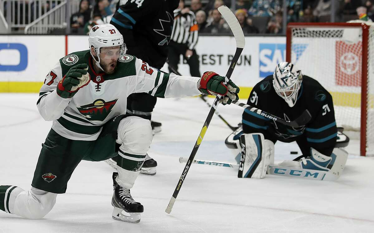 Minnesota Wild forward Alex Galchenyuk, left, celebrates after scoring a goal against San Jose Sharks' Martin Jones, right, in the second period of an NHL hockey game Thursday, March 5, 2020, in San Jose, Calif. (AP Photo/Ben Margot)