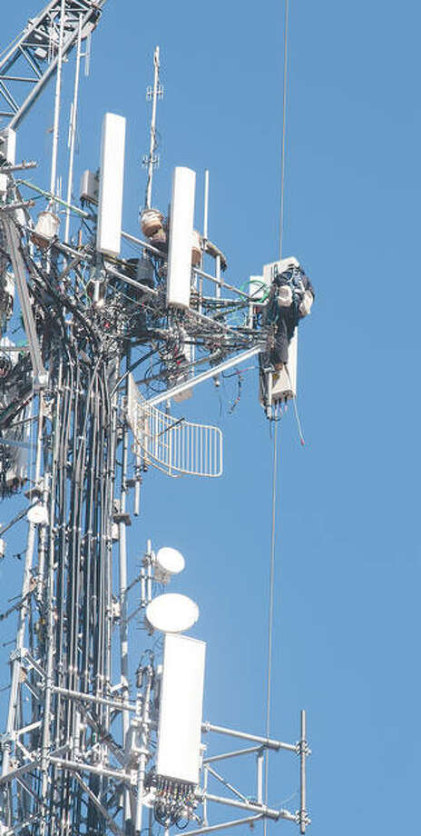 Felipe Jimenez (right) and Juan Saavedra (left) work 200 feet in the air Thursday, installing 5G antennas at the top of a structure in downtown Jacksonville. Both work for Mextel Communications of Chicago. The crew will be installing the antennas through next week. The next generation for mobile broadband is 5G, which can provide substantially faster download and upload speeds than the current 4G LTE connections.
