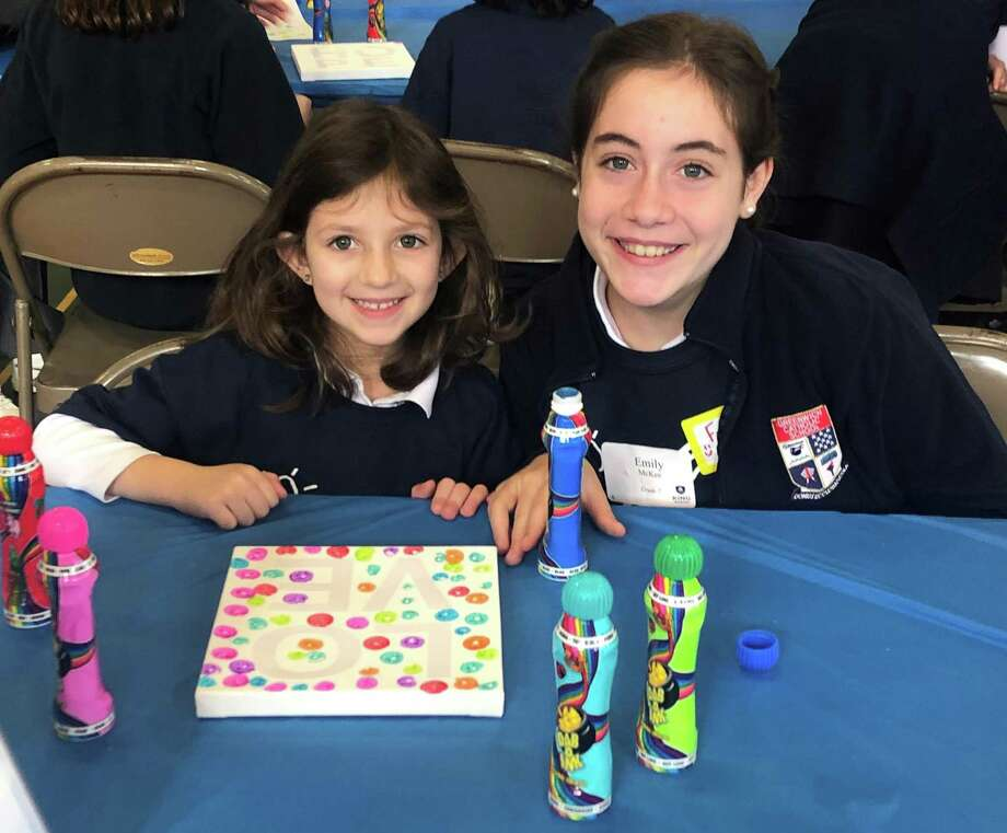 Greenwich Catholic School student Alyssa Baldwin and sixth-grader Frances Onorio take a break from making art during the school's second annual Together In Kindness Day. Greenwich Catholic School held its second annual Together In Kindness Day, when students made art and blankets and stuffed diaper bags with essentials for new moms, which the Malta House in Norwalk will distribute. Photo: Contributed