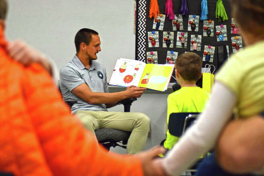 Professional soccer player for the St. Louis FC, Sam Fink, reads a Dr. Seuss book to a classroom full of District 7 students and family during Read Across America at Woodland Elementary School Thursday night. Photo: Tyler Pletsch|The Intelligencer