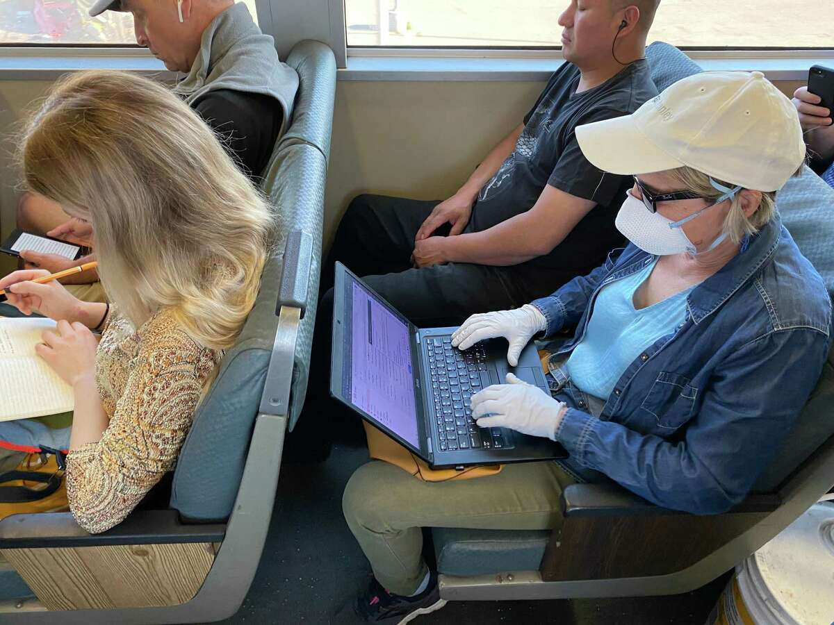 A person wearing a protective mask and gloves rides on a Bay Area Rapid Transit (BART) train car during the morning commute in Oakland, California.