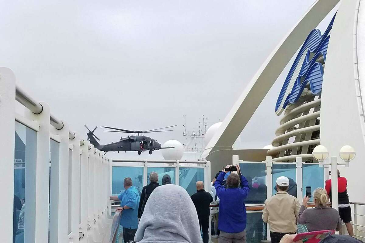 In this photo provided by Michele Smith, passengers look on as a Coast Guard helicopter hovers above the Grand Princess cruise ship Thursday, March 5, 2020, off the California coast. Scrambling to keep the coronavirus at bay, officials ordered a cruise ship with about 3,500 people aboard to stay back from the California coast Thursday until passengers and crew can be tested, after a traveler from its previous voyage died of the disease and at least two others became infected. A Coast Guard helicopter lowered test kits onto the 951-foot (290-meter) Grand Princess by rope as the vessel lay at anchor off Northern California, and authorities said the results would be available on Friday. Princess Cruise Lines said fewer than 100 people aboard had been identified for testing. (Michele Smith via AP)