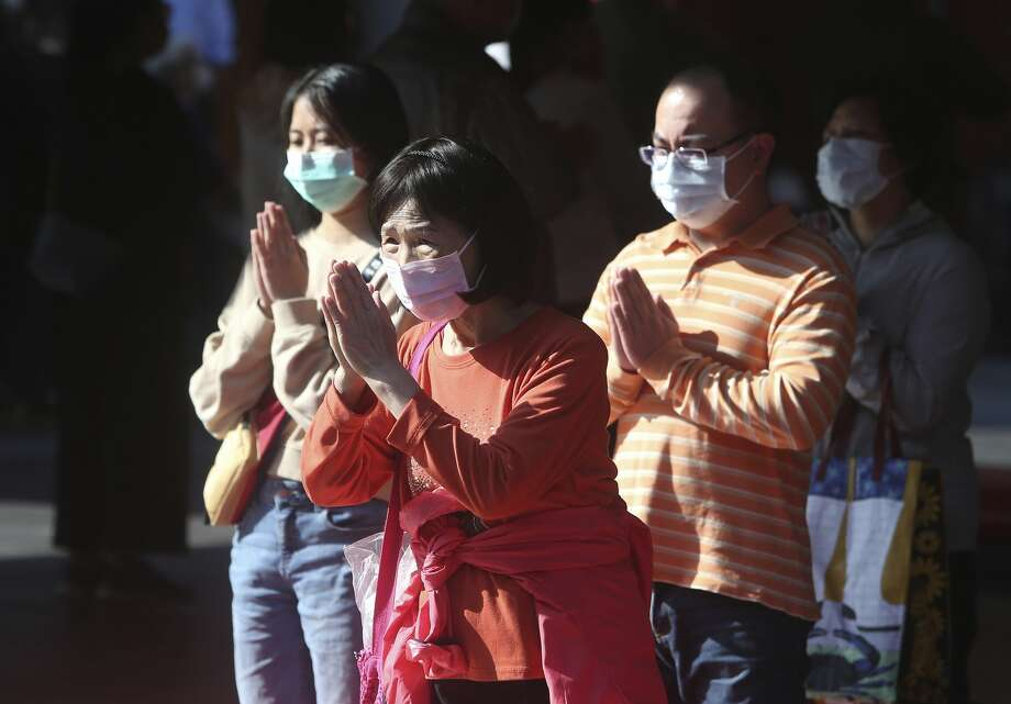 Worshippers wear face masks to protect against the spread of the coronavirus as they pray at the famous Hsing Tian Kong Temple in Taipei. Taiwan's timely, efficient response to the outbreak has saved lives. Photo: Chiang Ying-ying/Associated Press