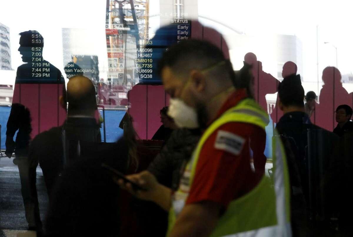 An LAX worker wears a mask amid fears of coronavirus at the Tom Bradley International Terminal at Los Angeles International Airport on Feb. 8. (Genaro Molina/Los Angeles Times/TNS)