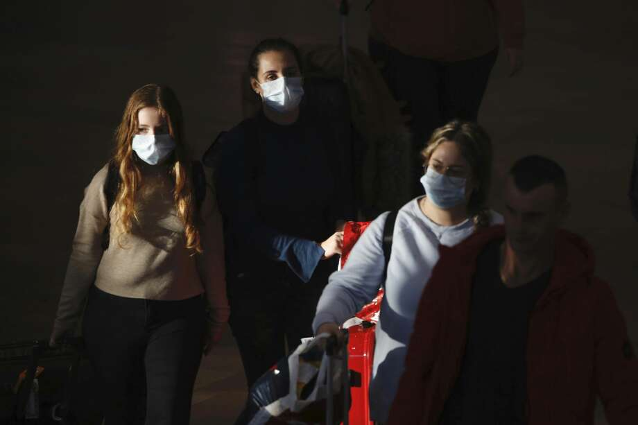 FILE - In this Thursday, Feb. 27, 2020 file photo, travelers wearing protective masks arrive at the Ben Gurion Airport, near Tel Aviv, Israel. A steep drop in business travel could be a gut punch to a tourism industry already reeling from the coronavirus outbreak, as big companies like Amazon try to keep employees healthy by banning trips. (AP Photo/Ariel Schalit, File) Photo: Ariel Schalit/Associated Press