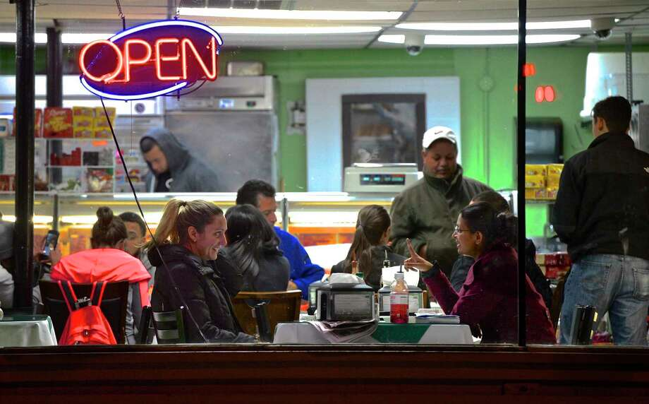Abhi Tangada, right, and Kendall Adams, both from Danbury, sit in the front window of Minas Carne Deli & Churrascaria, on Osborne Street in Danbury, and enjoy an after dinner conversation. Tuesday, November 10, 2015. Photo: H John Voorhees III / Hearst Connecticut Media / The News-Times
