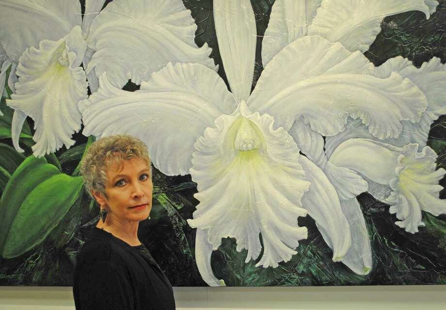 "Patricia Laspino in front of her painting ""Alice B,"" 2011. By immortalizing nature's own orchid masterpieces, Laspino's work seeks to enhance the understanding of our past and present infatuations with orchid species, and illuminate future expectations for our interaction with these magnificent plants, SM&NC says. Photo: SM&NC / Contributed Photo"