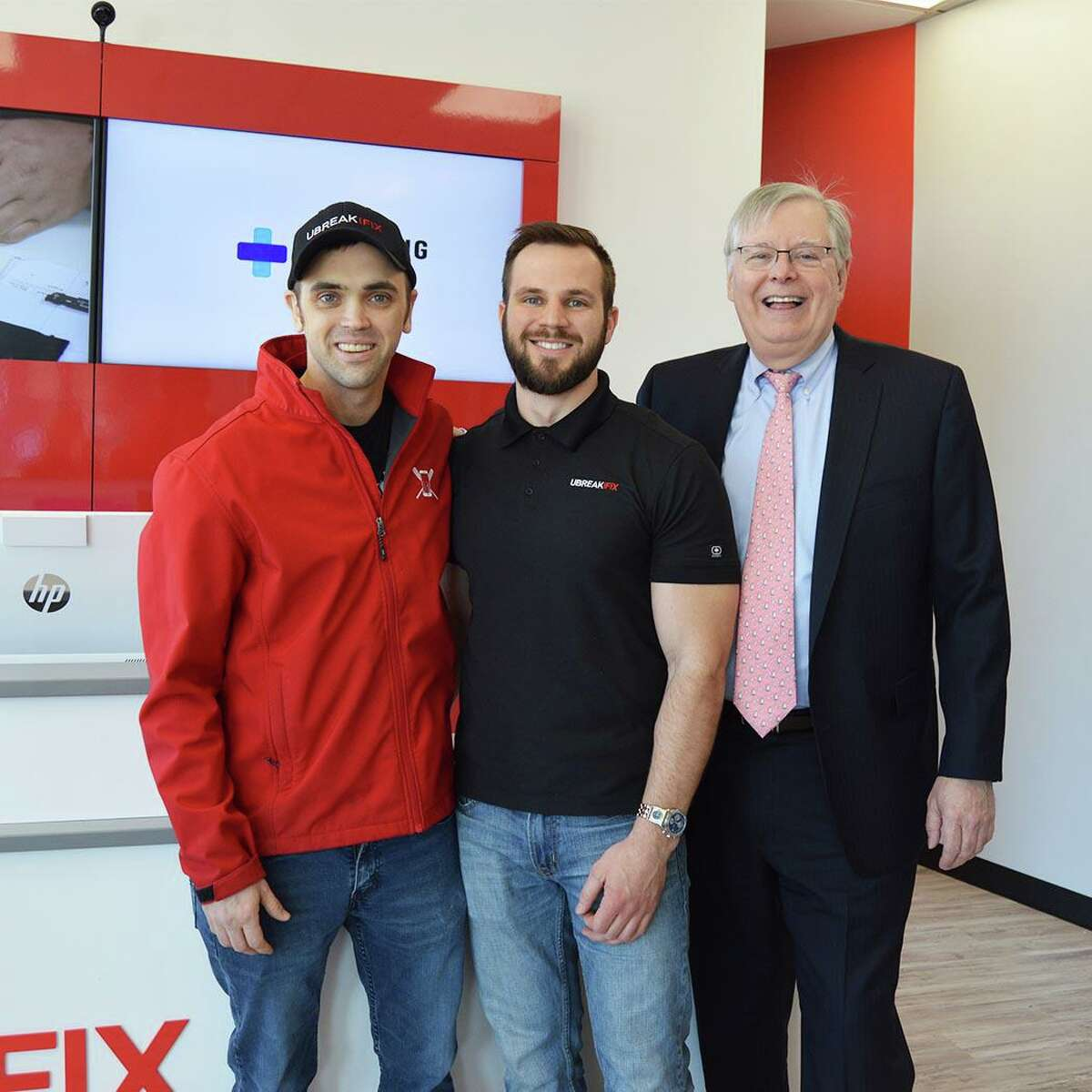 From left, UBreakiFix Stamford store owners Steven Gardner and Chris Laraia and Stamford Mayor David Martin attend a grand opening at the store at 123 High Ridge Road on Thursday, March 5, 2020.