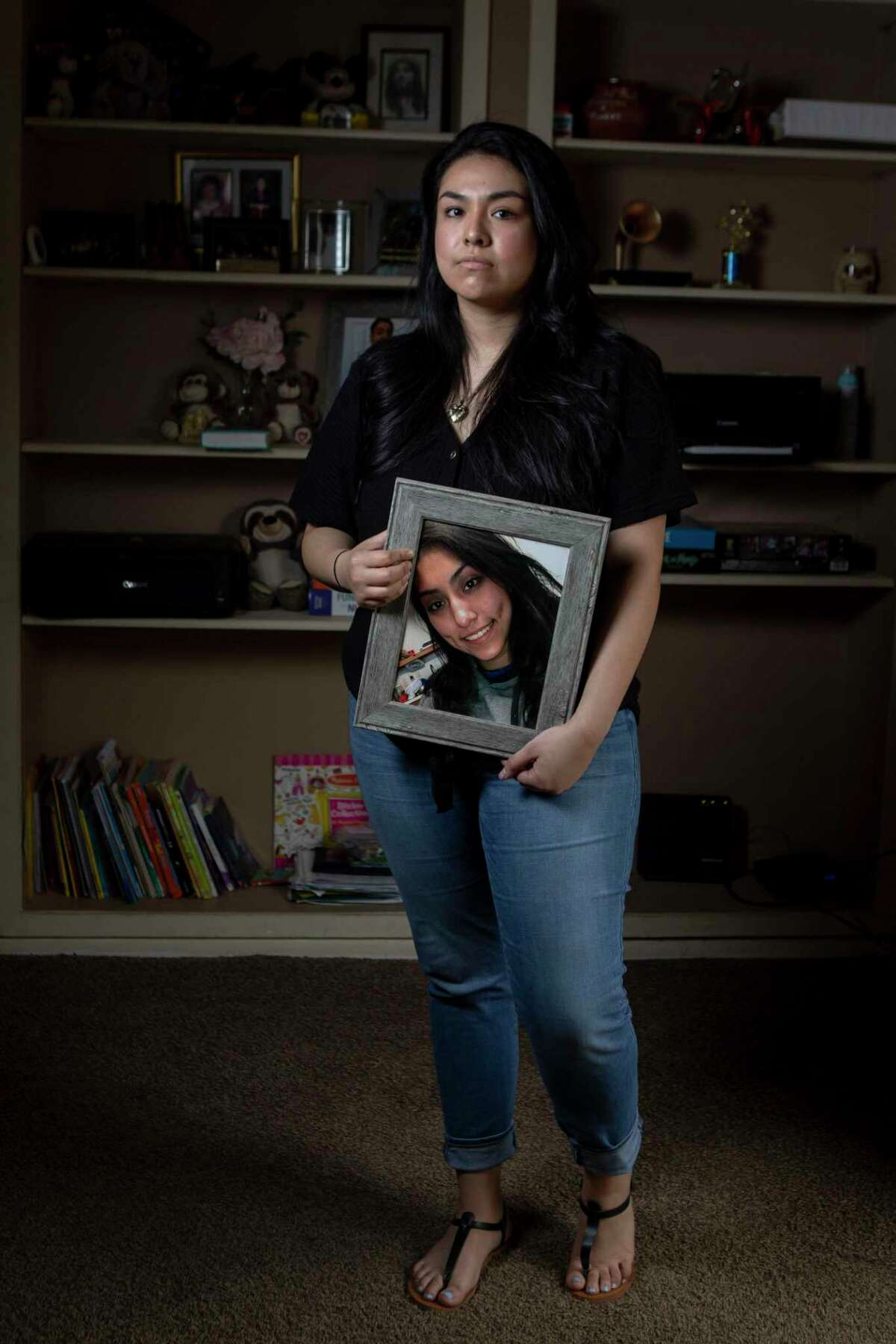 Destiny Herrera died in a 2019 car accident, a year before her foster dad Miguel Briseno is set to appear in court on charges of sexual assault. Herrera's older sister, Faith, holds her photo.