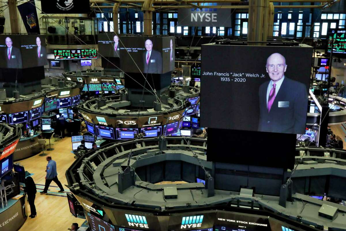 Images of Jack Welch appear on screens above trading posts on the floor of the New York Stock Exchange, Monday, March 2, 2020. (AP Photo/Richard Drew)