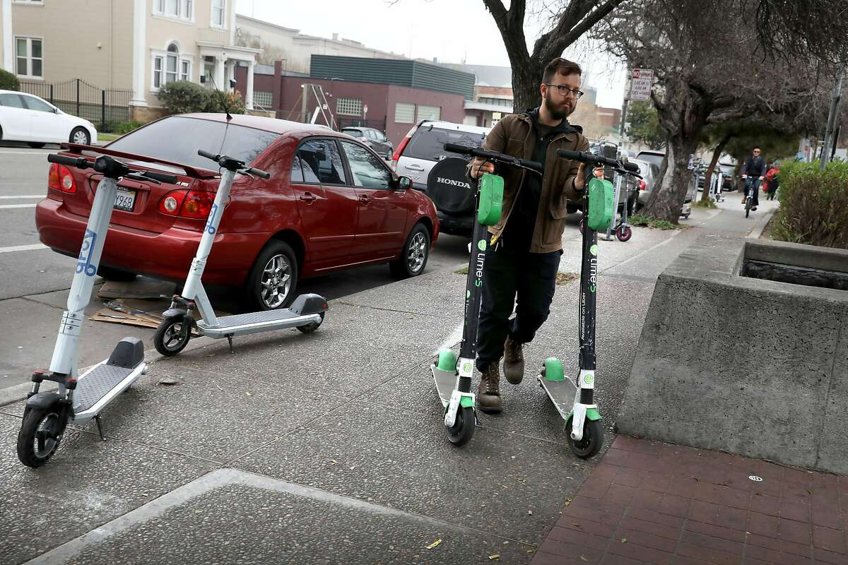 Lime operations lead Alfredo Sanchez retrieves scooters on 9th St. bringing them back to the Lake Merritt Bart station on Thursday, March 5, 2020, in Oakland, Calif.