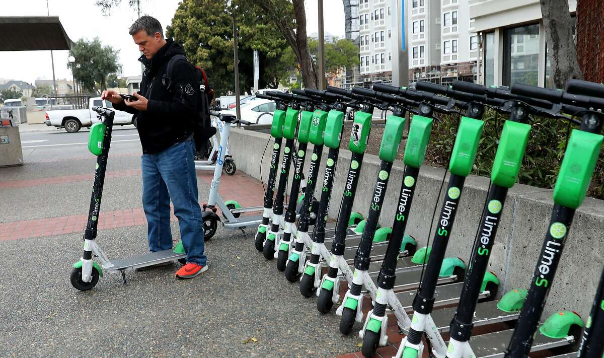 Alejandro Caminos from Valenzuela gets ready to use a Lime scooter from the Lake Merritt Bart station on Thursday, March 5, 2020, in Oakland. Lime is adding 1,000 scooters in San Francisco.