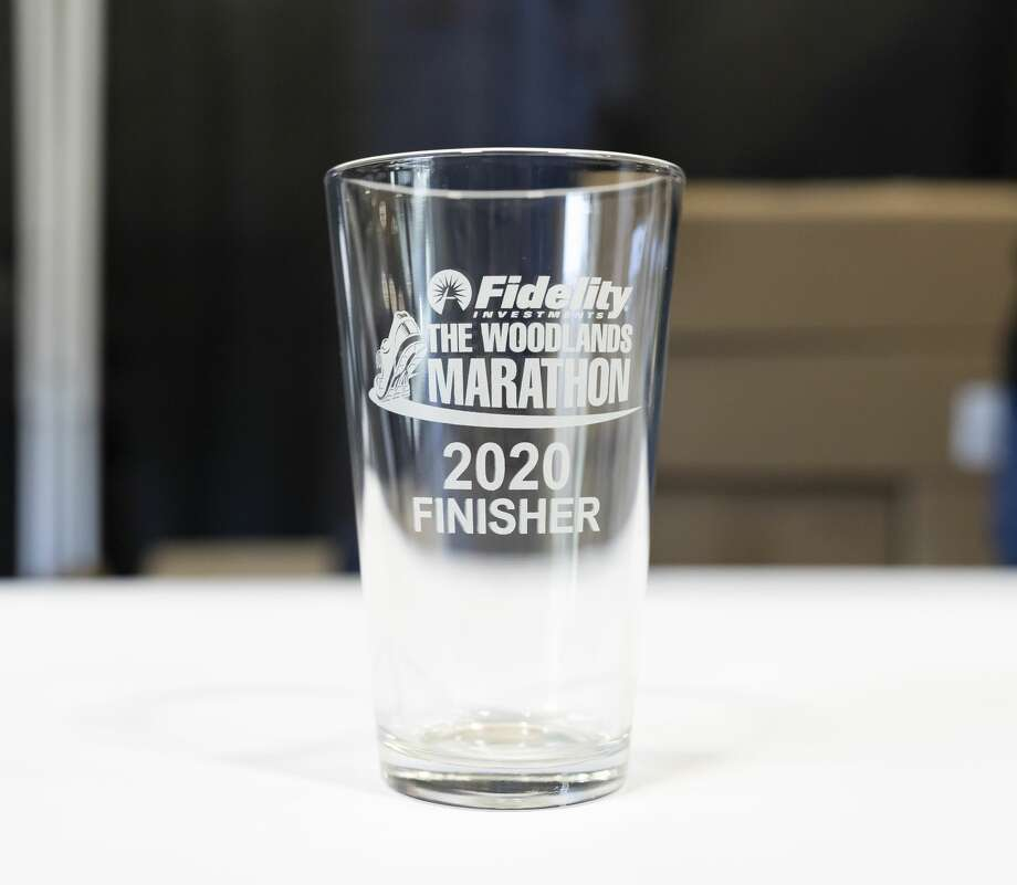Runners who were registered for the full marathon received glassware at The Cynthia Woods Mitchell Pavilion in the Woodlands, Friday, March 6, 2020.An estimated 9,000 people are registered to participate in this year's marathon. Photo: Gustavo Huerta/Staff Photographer
