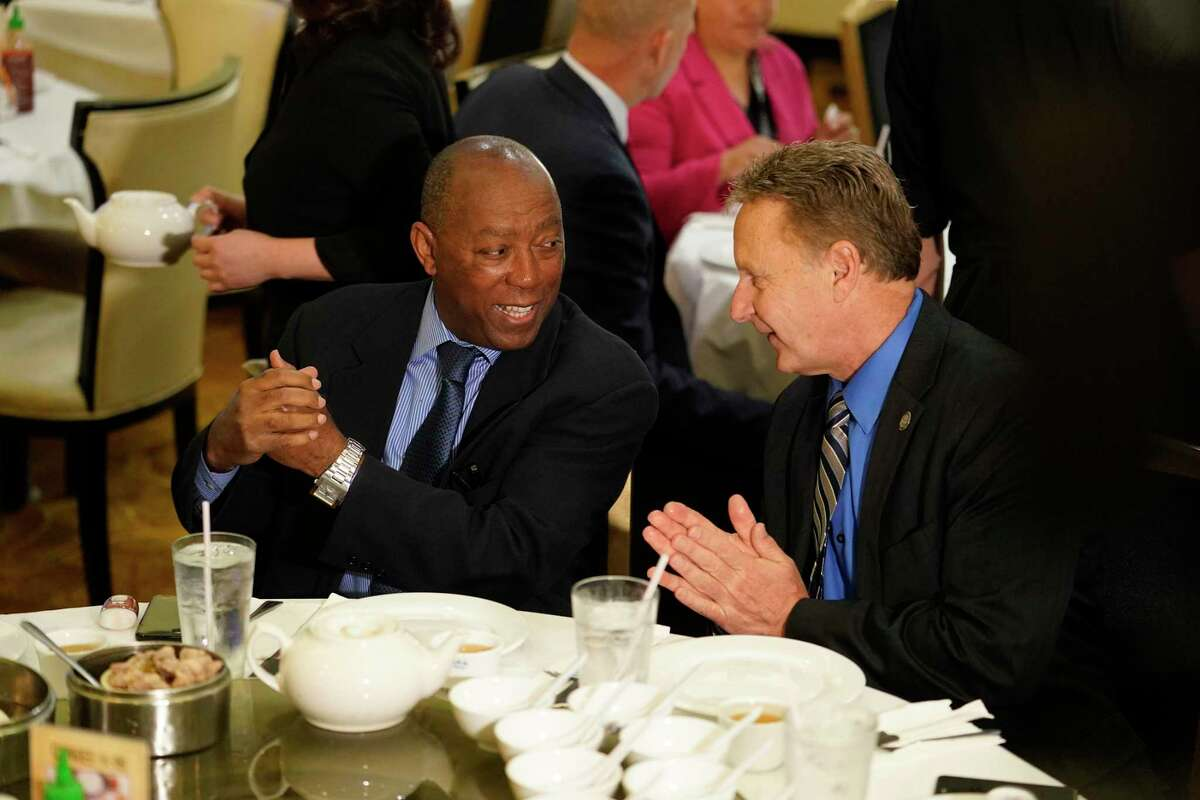 Mayor Sylvester Turner, left, and George Buenik, Public Safety director, right, use hand sanitizer before they eat lunch at Ocean Palace Restaurant, 11215 Bellaire Blvd., Thursday, March 5, 2020, in Houston. Mayor Sylvester Turner gathered with a couple dozen staff members and city officials for lunch at Ocean Palace in Asiatown in a bid to alleviate concerns and tamp down on rumors about COVID-19.