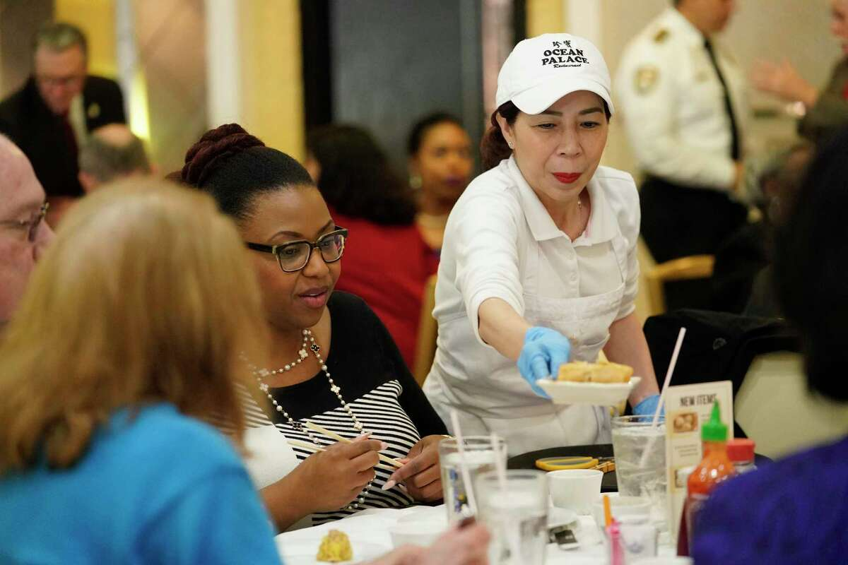 Tieu Buu Luong serves lunch at Ocean Palace Restaurant, 11215 Bellaire Blvd., Thursday, March 5, 2020, in Houston. Mayor Sylvester Turner gathered with a couple dozen staff members and city officials for lunch at Ocean Palace in Asiatown in a bid to alleviate concerns and tamp down on rumors about COVID-19.