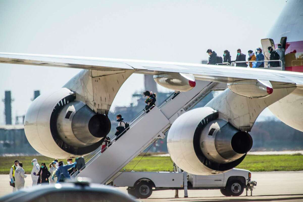 Evacuees at risk of carrying the coronavirus arrive at Joint Base San Antonio-Lackland aboard a chartered Boeing 747 on Feb. 7, 2020.