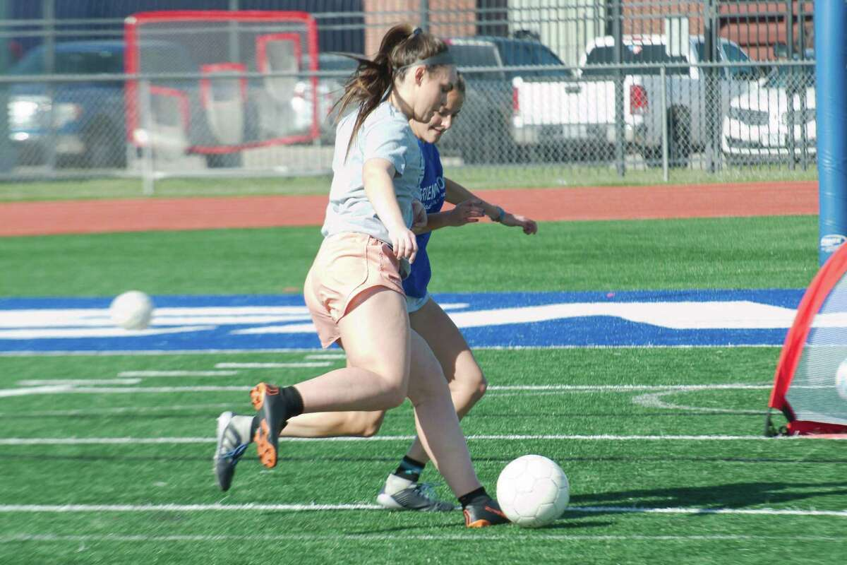 Katie Reyes and Bailey Havens participate in a one-on-one drill during Friendswood girls' soccer practice Thursday at Friendswood High School.