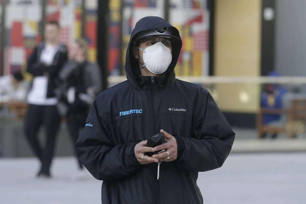 An man who asked to remain unidentified wears a mask because of the coronavirus outbreak outside of the Chase Center before an NBA basketball game between the Golden State Warriors and the Toronto Raptors in San Francisco, Thursday, March 5, 2020. (AP Photo/Jeff Chiu)