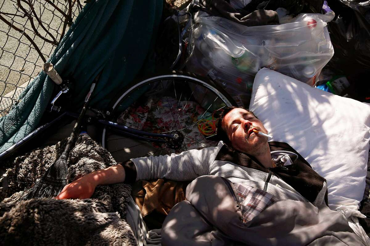 Mike McAuliffe, who is homeless, sleeps at an encampment along Treat Street on Wednesday, March 4, 2020 in San Francisco, Calif.