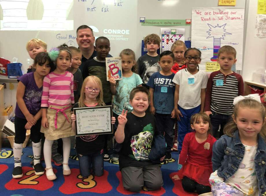 Members of the Conroe Noon Lions Club participated in the annual 'Reading Across America'; by reading to ALL the classes at their adopted school - Reaves Elementary. Pictured in background, Lion Warner Phelps, who honored his class as 'Best Kids Ever'. Photo: Courtesy Photo