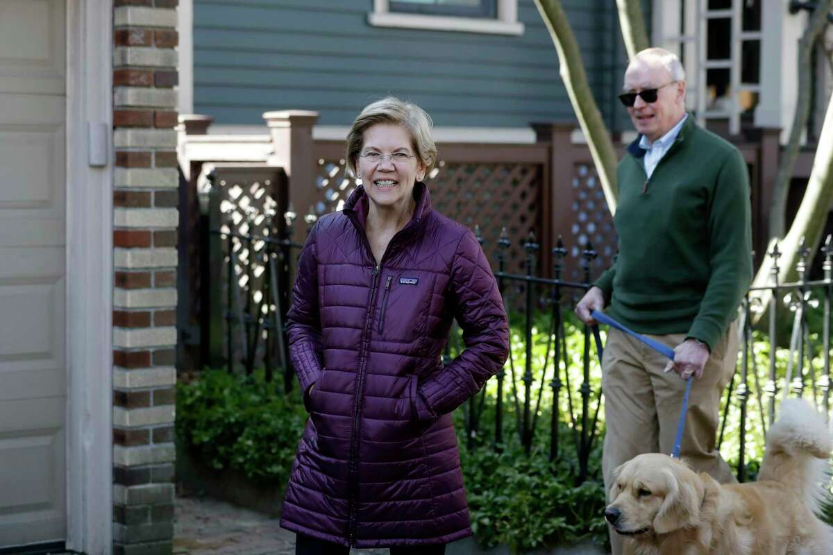 Sen. Elizabeth Warren, D-Mass., left, with her husband Bruce Mann, right, and dog Bailey, approach members of the media outside her home in Cambridge, Mass., March 5 as she arrives to speak to the media after she dropped out of the Democratic presidential race.