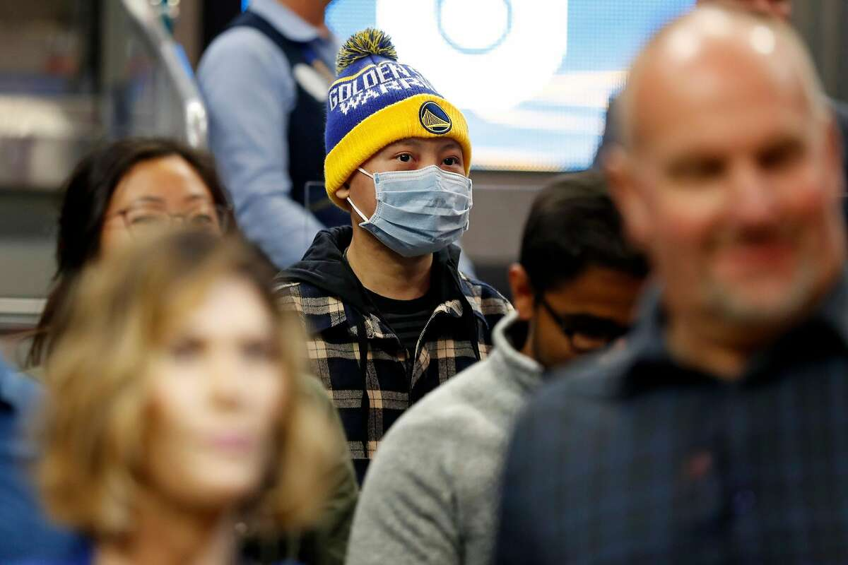 A Golden State Warriors' fan wears a surgical mask during Warriors' game against Toronto Raptors at Chase Center in San Francisco, Calif., on Thursday, March 5, 2020.