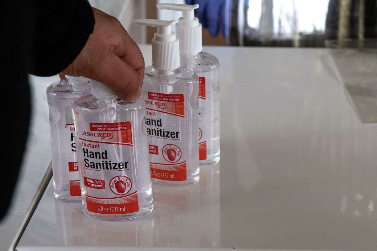 A customer buys bottles of hand sanitizer in a coronavirus pop-up store in Washington, DC, on March 6, 2020. - As supplies of face masks and hand sanitizer have dwindled due to the outbreak of Covid-19,