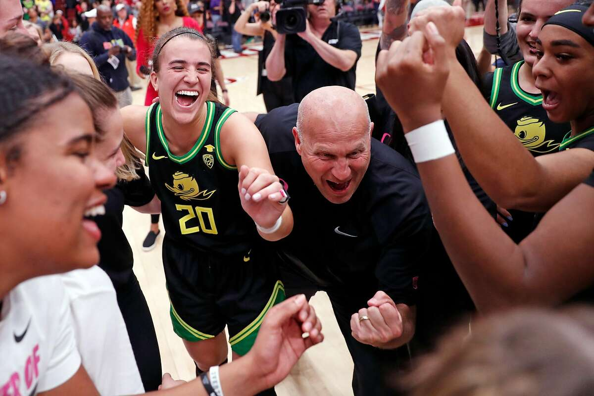 """Oregon""""s Sabrina Ionescu and head coach Kelly Graves celebrate after Ducks' 74-66 win in Pac 12 women's basketball game at Maples Pavilion in Stanford, Calif., on Monday, February 24, 2020."""