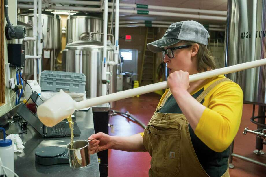 Leah Witkoske, a brewer at Midland Brewing Company, takes a sample of wort to test its pH and gravity as she brews a batch of beer Thursday at Midland Brewing Company. Witkoske has invited female Michigan brewers, as well as female community members and MBC staff, to join her this Sunday in crafting a beer she formulated in honor of International Women's Day and International Women's Collaboration Brew Day, which both fall on Sunday. (Katy Kildee/kkildee@mdn.net)