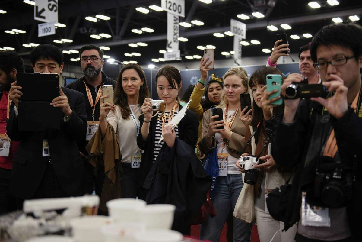 Attendees take photographs as a robot prepares breakfast at the South By Southwest (SXSW) conference in Austin, Texas, U.S., on Sunday, March 10, 2019. The SXSW conference provides an opportunity for global professionals at every level to participate, network, and advance their careers. Photographer: Callaghan O'Hare/Bloomberg