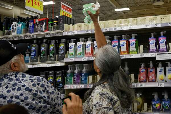 While the Trump administration has muddled its messages about the coronavirus, the run on hand sanitizer reflects public concern, a reader says. Here, shoppers reach for the last bottles of hand sanitizer bottles at the H-E-B in Olmos Park last week.