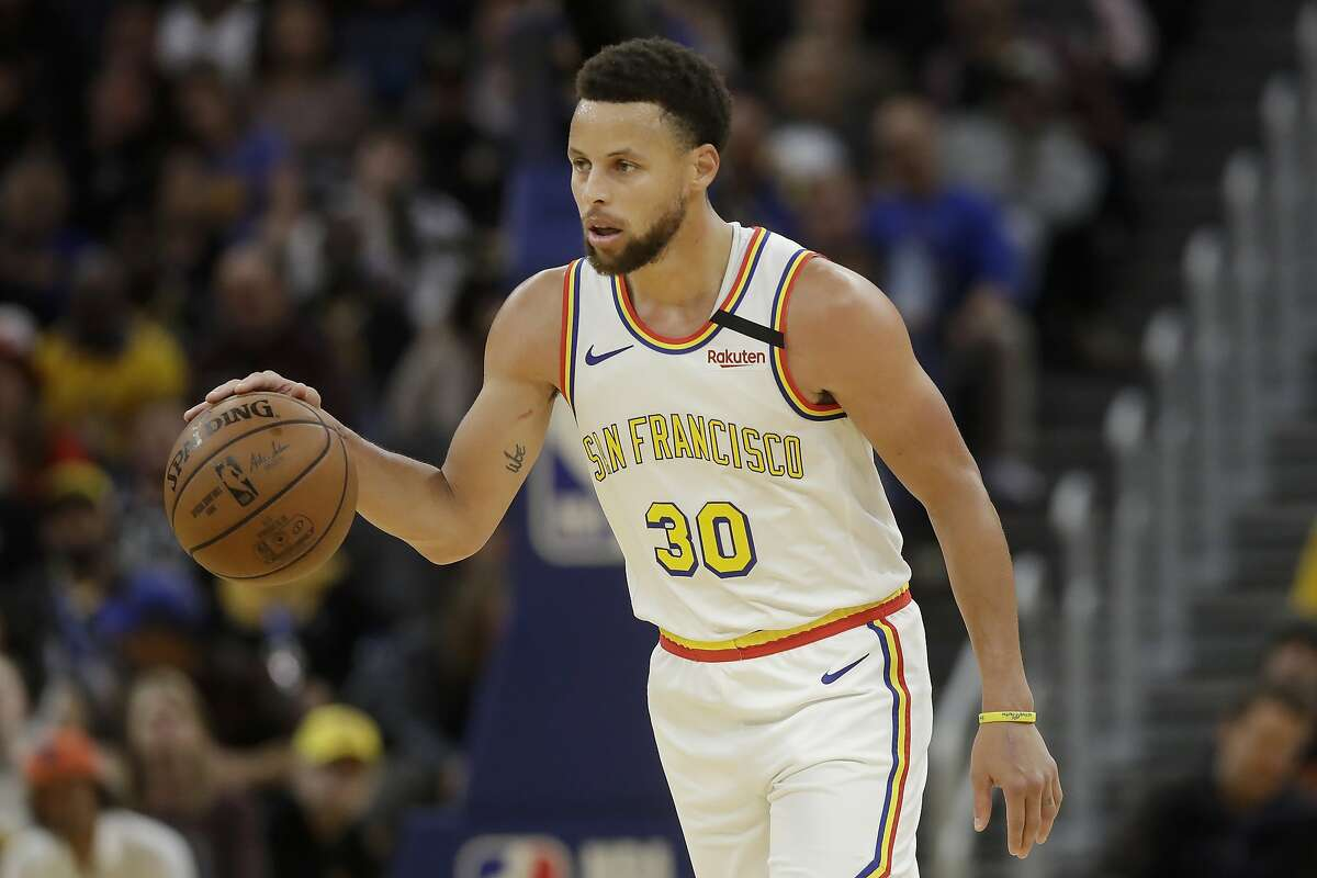 Golden State Warriors guard Stephen Curry (30) dribbles the ball up the court against the Toronto Raptors during the second half of an NBA basketball game in San Francisco, Thursday, March 5, 2020. (AP Photo/Jeff Chiu)