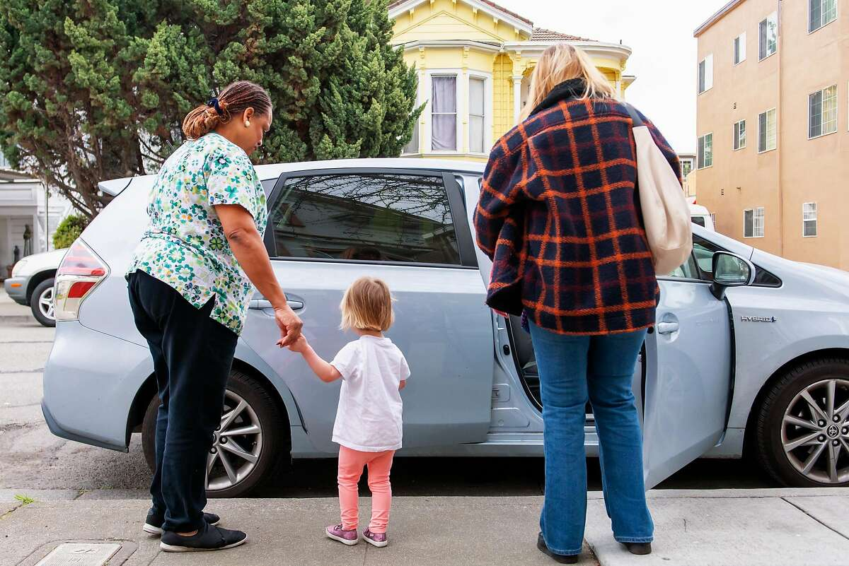Nancy Harvey (L) walks Hanna Prechtl (1 1/2 yr. old), out of Lil Nancy's Primary Schoolhouse school with Hanna�s mother Ellen Vanderlaan at an early pick up from school in order for the staff to do an extra-deep cleaning because of coronavirus fears on February 6, 2020 in Oakland, Calif.
