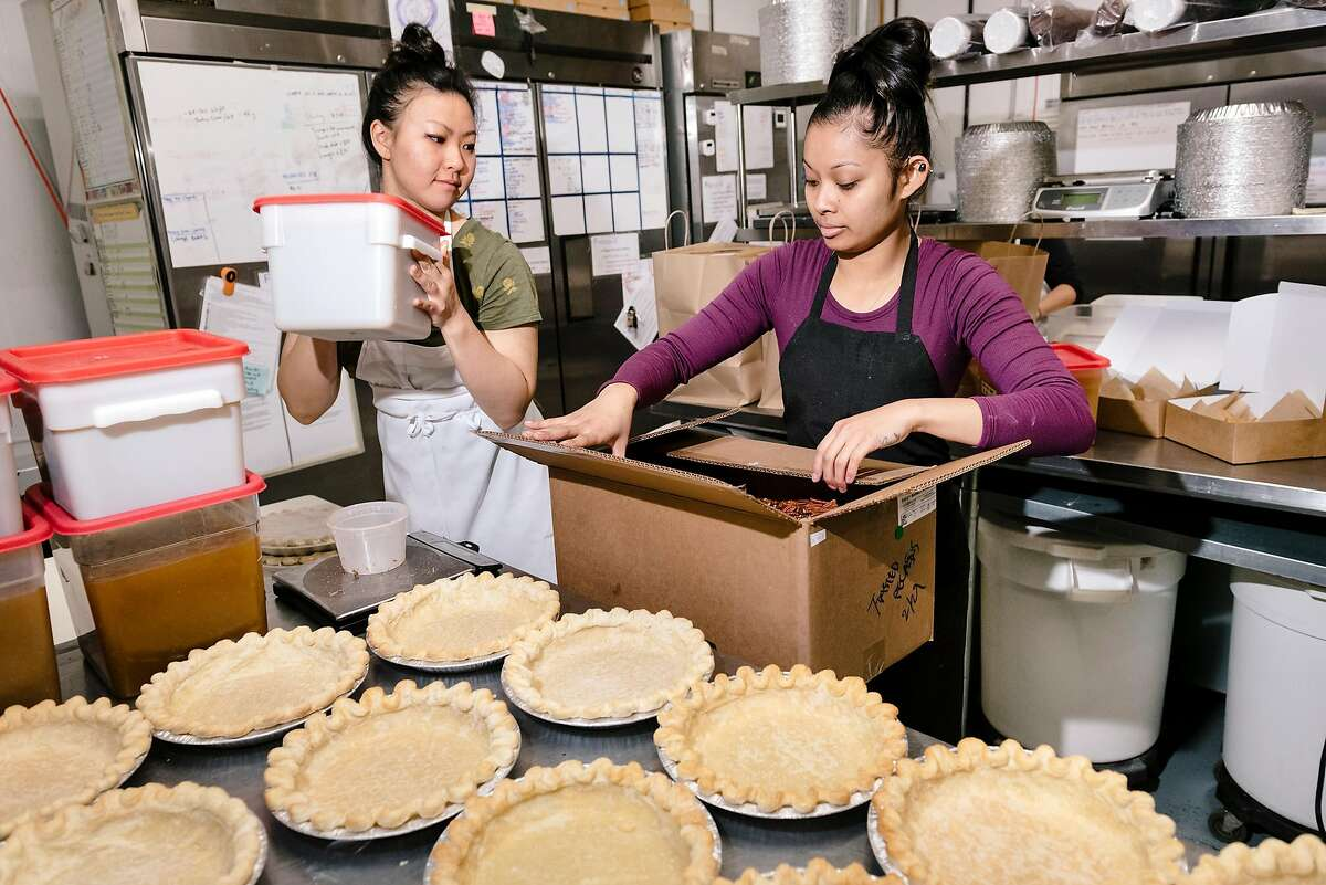 Gigi Huang, left, and Julie Tran work on making pies at Three Babes Bakeshop in San Francisco, California, on Friday, March 6, 2020. Three Babes Bakeshop, which largely caters to local San Francisco tech employers, is seeing a dramatic decrease in business since tech companies are having employees work from home due to fears over the Coronavirus, and is having to make cutbacks in their production numbers and potentially may have to cut some workers' hours.
