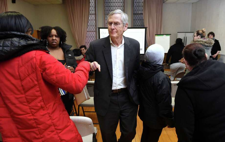 Attorney David Rosen (center) fist bumps former Church Street South resident Personna Noble (left) after giving a presentation on a class action settlement for former residents of the housing complex at Trinity Lutheran Church in New Haven on March 6, 2020. Photo: Arnold Gold / Hearst Connecticut Media / New Haven Register