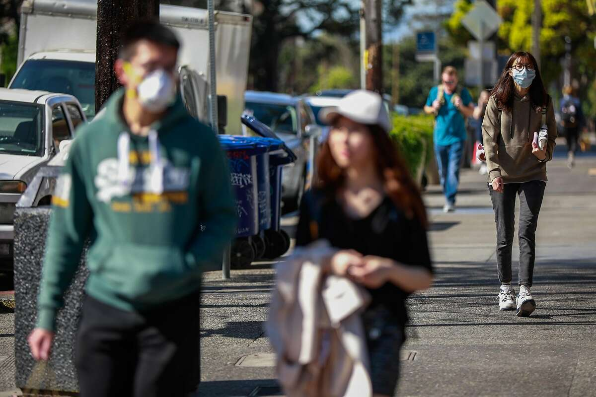 People wear masks while walking on Durant Avenue on Wednesday, March 4, 2020 in Berkeley, California. A Berkeley resident recently tested positive to the coronavirus.