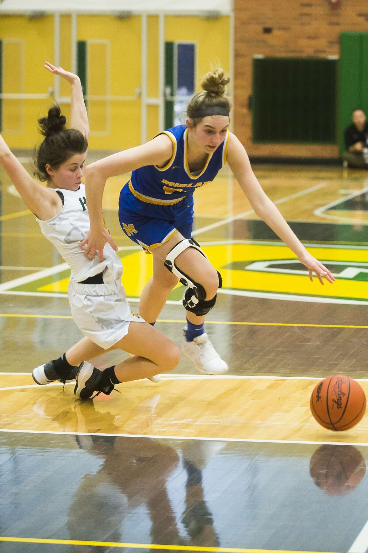 Midland's Anna Tuck dribbles past Dow's Chloe McVey during the Chemics' Division 1 district championship loss to Dow Friday, March 6, 2020 at H. H. Dow High School. (Katy Kildee/kkildee@mdn.net)