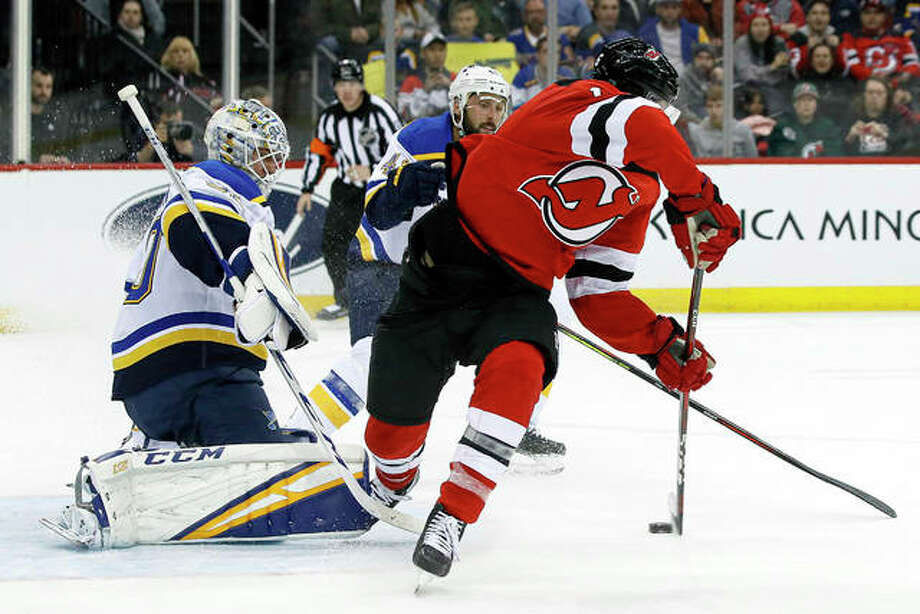 New Jersey Devils center Kevin Rooney, right, puts the puck into the net against Blues goaltender Jordan Binnington, left, before the goal was disallowed for interference in the second period of Friday night's game in Newark, N.J.