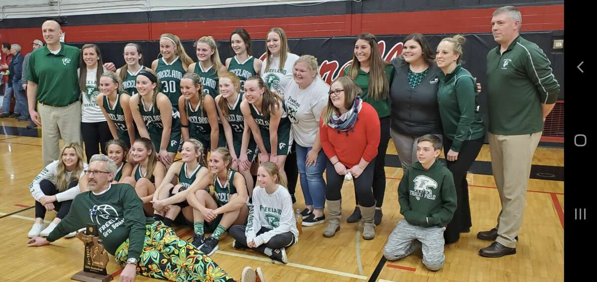 Freeland's girls' basketball team poses with its trophy after beating Bay City John Glenn in Friday's Division 2 district final.