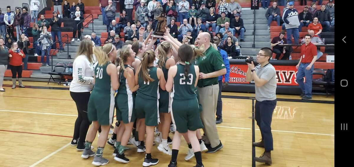 Freeland's girls' basketball team celebrates on the court following its Division 2 district final win over Bay City John Glenn on Friday.
