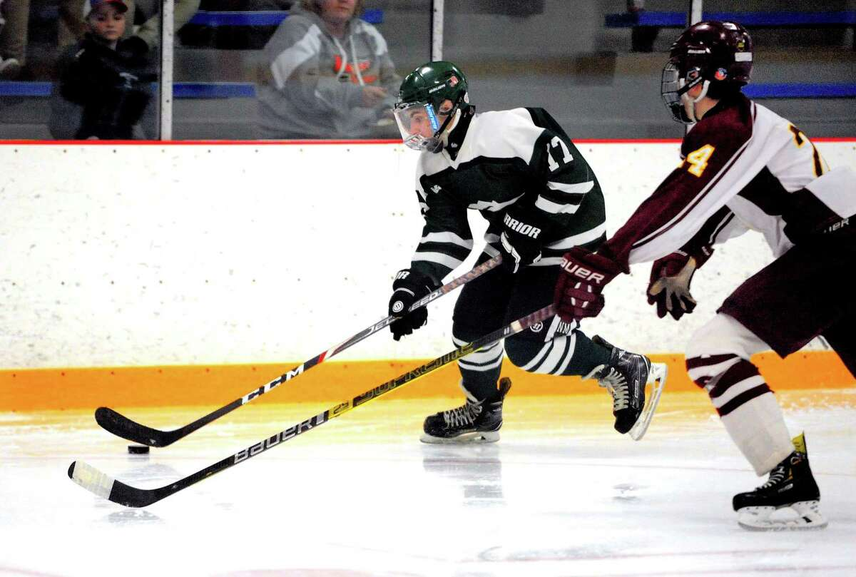 New Milford's Daniel Gallagher (17) drives the puck as Sheehan's James Stratton (24) chases during SCC Div. III Championship hockey action in West Haven, Conn., on Friday Mar. 6, 2020.