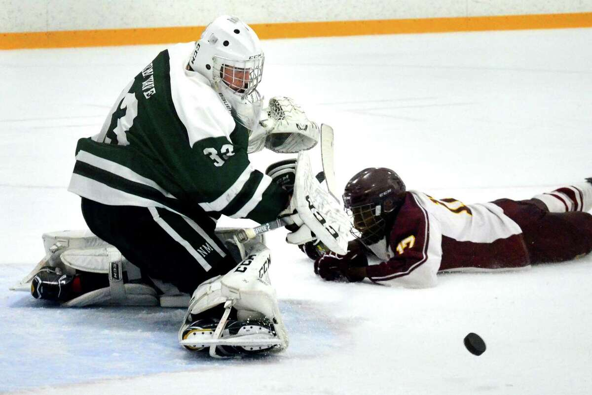 New Milford goalie Logan Lucas deflects a Sheehan goal attempt during SCC Div. III Championship hockey action in West Haven, Conn., on Friday Mar. 6, 2020.